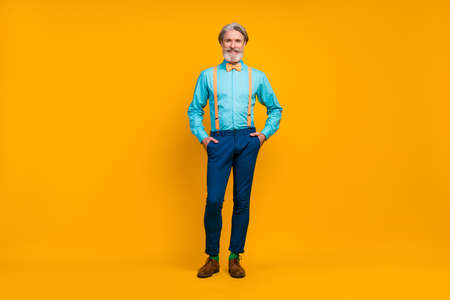 Full length photo of cool trendy grandpa hold hands pockets charismatic person stylish look clothes wear shirt suspenders bow tie pants boots, socks isolated yellow color background