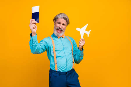 Photo of cool grandpa hold paper air plane recommend new airline show tickets low cost price traveler wear blue shirt suspenders, bow tie pants isolated yellow color background
