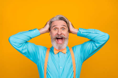 Closeup photo of cool clothes crazy white haired grandpa open mouth see sale shopping advert arms on head wear blue shirt suspenders bow tie, isolated yellow color background