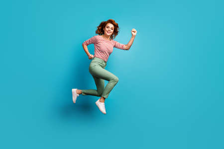 Full body profile photo of beautiful funny lady jump high speed rush final season shopping wear casual red white shirt green trousers footwear isolated blue color background