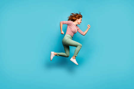 Full body profile photo of funny lady jump high speed rushing black friday season shopping wear casual red white shirt green trousers footwear isolated blue color background Standard-Bild