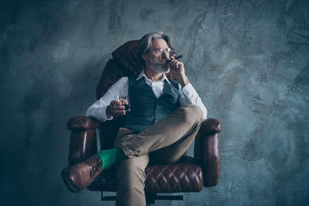 Masculine confident old man shareholder sit chair relax hold glass brandy smoke cigarette look wear white shirt brown luxury pants green socks isolated grey concrete wall color background