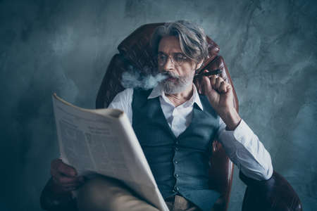 World economy political news concept.Luxury classy chic dandy old man company owner morning newspaper reader sit chair smoke cigar wear shirt brown pants trousers isolated grey color background Stock Photo