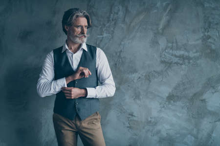 Portrait of stunning old dandy man adjust button sleeves prepare for work job meeting look good copy space wear brown shirt outfit isolated over concrete wall grey color background Banque d'images