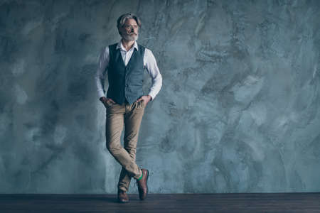 Full body photo of macho senior business man neat beard hairdo seriously look side empty space minded wear specs shirt waistcoat pants isolated concrete grey color wall background