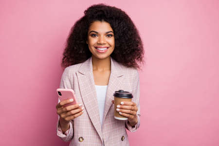 Photo of attractive beautiful dark skin business lady hold telephone drink takeaway hot beverage coffee break wear checkered blazer isolated pastel color background