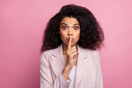 Hush private novelty. Astonished marketer afro american girl put index finger lips dont tell managers company speechless secrets wear plaid stylish jacket suit isolated pastel pink color background