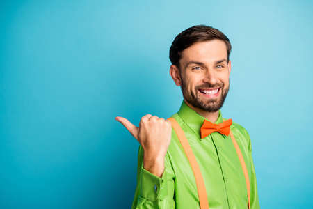 Close-up portrait of his he nice attractive content cheerful guy pointing thumb demonstrating copy space look new idea isolated on bright vivid shine vibrant blue green turquoise color background