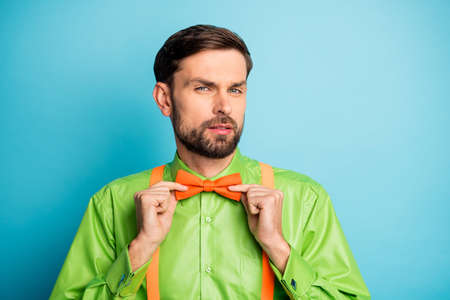 Close-up portrait of his he nice imposing elegant guy macho metrosexual fixing bow-tie preparing festal look isolated over bright vivid shine vibrant blue green teal turquoise color background