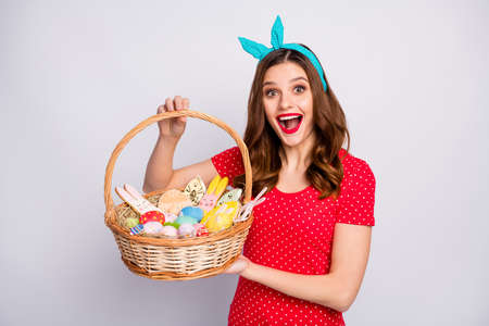 Shocked surprised redhair girl hold big wicker basket painted colorful blue eggs sweet easter confectionery shaped bunny wear red t-shirt retro style t-shirt isolated grey color background