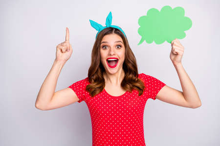 Omg unbelievable. Astonished crazy girl hold green paper card bubble speech think thoughts get brilliant idea solution raise index finger up wear retro style isolated grey color background 스톡 콘텐츠