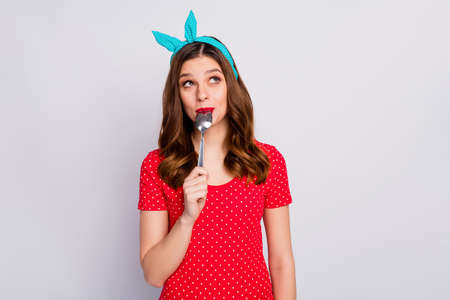 Charming cute pretty girl lick spoon look copyspace think thoughts dream about delicious tasty dinner dessert wear vintage style t-shirt dotted blue red isolated over grey color background 스톡 콘텐츠