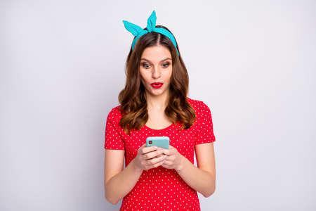 Portrait of astonished girl use smart phone read social media information impressed scream wow ogm wear good look clothes isolated over grey color background Banque d'images