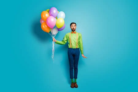 Full length body size view of his he nice attractive funky amazed wondered cheerful guy holding in hands air balls isolated on bright vivid shine vibrant blue green teal turquoise color background
