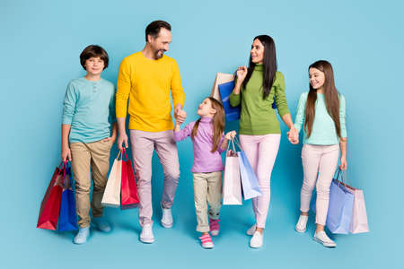 Full length body size view of nice attractive confident cheerful cheery big full family carrying bags new things clothes boutique going isolated on bright vivid shine vibrant blue color background
