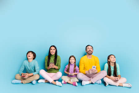 Nice attractive lovely charming cheerful cheery big full family pre-teen kids sitting in lotus pose using gadget looking up copy space isolated on bright vivid shine vibrant blue color background