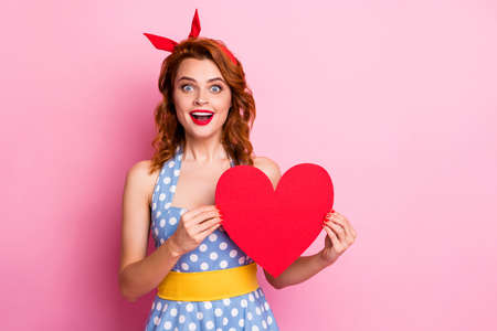 Photo of charming funny lady hold big red paper heart presenting best way to say I love you wear headband dotted dress yellow belt isolated pink color background