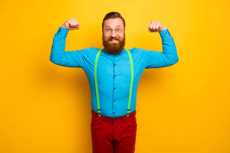 Photo of attractive funny toothy guy raise fists arms presenting perfect shape biceps after training gym wear blue shirt green suspenders red pants isolated yellow color background
