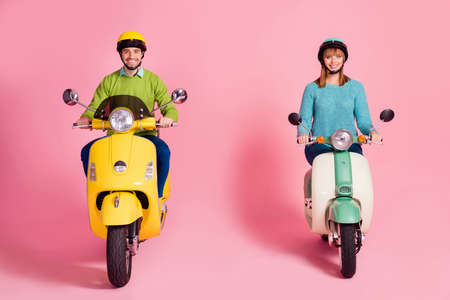 Full length photo of funny cheerful lady guy driving two vintage moped spend vacation together safe road speed wear casual jumper, colorful headgear isolated pink color background