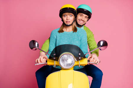 Im scared. Photo of nice lady guy two people couple trying drive vintage yellow moped eyes full fear afraid to fall down wear casual outfit headgear isolated pink color background 스톡 콘텐츠