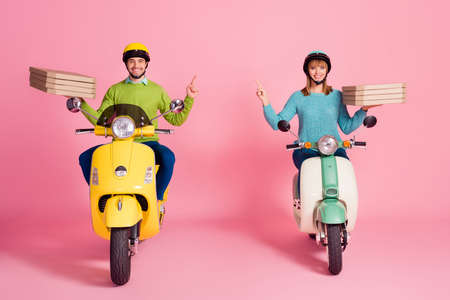 Full body photo of funny lady guy drive two vintage moped carry paper pizza boxes direct finger empty space courier wear casual jumper headgear isolated pink color background