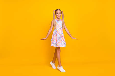 Full body photo of funny beautiful little lady good mood pretty long tails playful walk street wear plaid summer sun dress white sneakers isolated yellow shine color background