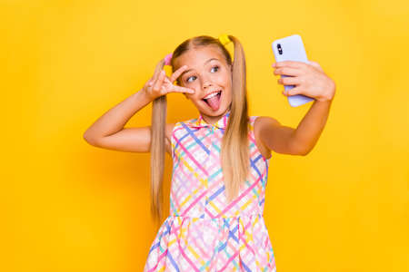 Photo of pretty small lady hold telephone influencer make selfies blog showing v-sign symbol stick tongue out mouth wear checkered summer dress isolated bright color background Stock Photo