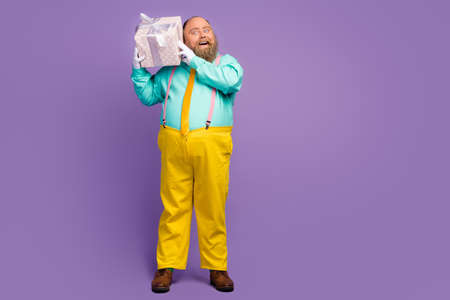 Full length photo astonished crazy shocked man big abdomen hold package anniversary party celebration shake wear pants teal shine pink suspenders footwear isolated purple color background