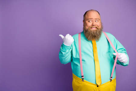 Positive cheerful overweight man pull pink suspenders point thumb copyspace recommend suggest select adverts promo wear turquoise yellow pants isolated vibrant color background