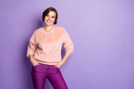 Photo of amazing youngster lady easy-going person good mood toothy smiling wear casual stylish pink sweater lilac pants isolated purple color background Stock Photo