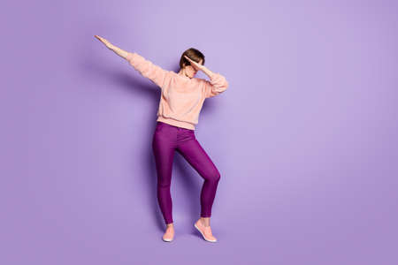 Full length photo of funky lady dancing strange modern moves disco party students hide eyes palm raise hands wear casual stylish sweater pants isolated purple color background