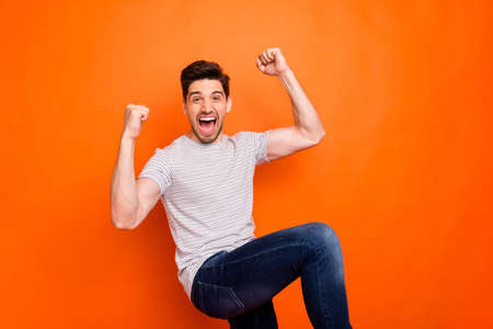 Photo of crazy funky guy yelling loud open mouth raise fists sportive cheerleader rejoicing best win team wear casual striped t-shirt jeans isolated bright orange color background
