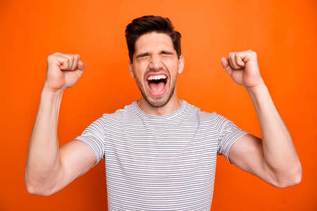 Photo of crazy funky energetic guy yelling loud open mouth best feelings watch football match game raise fists wear casual striped t-shirt isolated bright orange color background