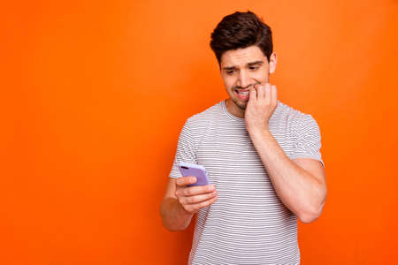 Oh no. Photo of terrified millennial guy hold telephone hand biting fingers read awful boss letter did bad thing wear striped t-shirt isolated bright orange color background