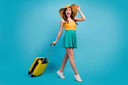 Full size profile photo of pretty lady traveler rolling suitcase walking airport flight check-in good mood resort tour wear mini summer dress hat shoes isolated blue background Zdjęcie Seryjne