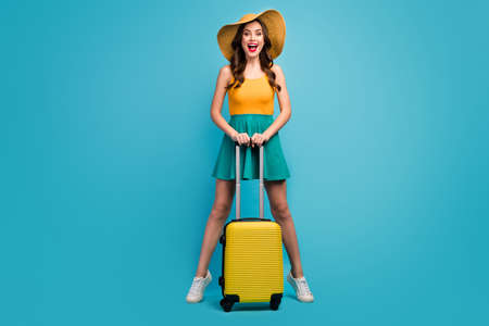 Full size photo of pretty lady traveler hold rolling suitcase luggage airport flight check-in good mood stand tip-toes wear sun specs short summer dress hat shoes isolated blue background Zdjęcie Seryjne