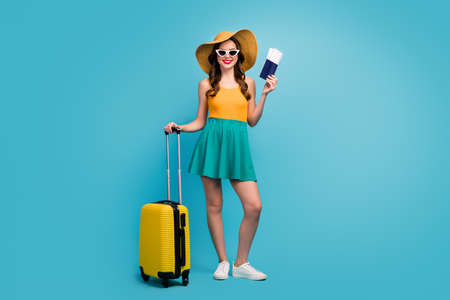Full size photo of pretty lady traveler hold passport tickets rolling suitcase registration airport plane flight wear sun specs short summer dress headwear shoes isolated blue background
