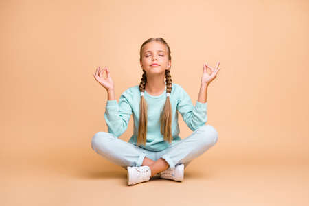 Full length photo of beautiful little lady sit floor legs crossed eyes closed fingers together lotus position meditating wear blue sweater jeans footwear isolated beige color background