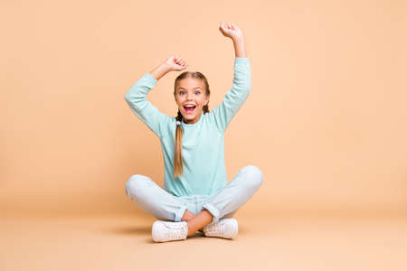 Goal. Full body photo of beautiful little lady raise fists watching sport match excited fan sit floor legs crossed wear blue sweater jeans footwear isolated beige color background