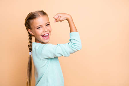 Profile photo of beautiful excited little lady ambitious person raise fist celebrating successful training workout wear blue pullover isolated beige pastel color background