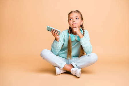 Full body photo of beautiful little lady listen earphones song sit floor legs crossed boring lesson school waiting go home wear blue sweater jeans footwear isolated beige color background