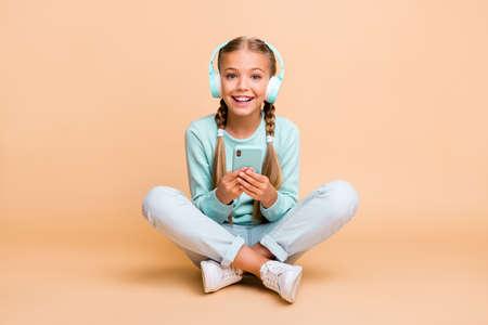 Full body photo of beautiful funny little lady enjoy listen earphones song good mood sit floor legs crossed wear blue pullover jeans footwear isolated beige color background
