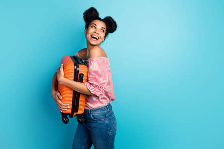 Profile photo of funny pretty dark skin lady hold big heavy suitcase enjoy traveling look side empty space wear striped red white off-shoulders blouse jeans isolated blue color background