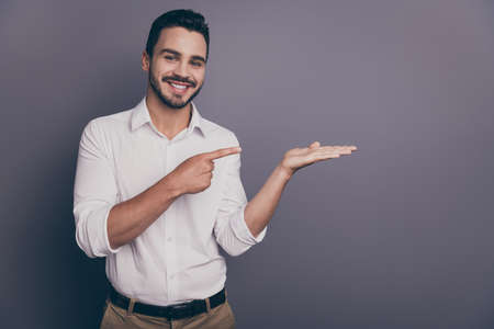 Photo of handsome business guy sales man indicating finger open palm advising novelty product nice offer low price wear white office shirt pants isolated grey color background