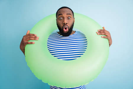 Photo of funny speechless dark skin guy hold green life buoy ready swim ocean sea traveler see sale banner advert not believe eyes wear striped sailor shirt isolated blue color background