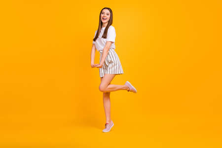 Full size profile photo of funny lady walking down street enjoy sunny day flirty mood wear casual white t-shirt striped shorts shoes isolated vibrant yellow color background