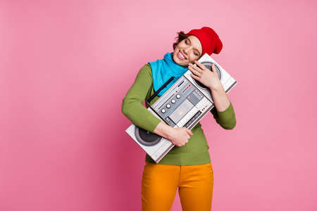 I love you music. Peaceful cheerful youth girl hug spring boombox close eyes dream rock party concert wear green blue sweater yellow pants style trendy trousers isolated pink color background Imagens
