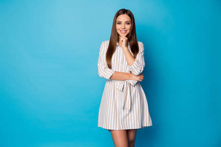 Photo of pretty attractive lady good mood beaming smile hold hand on chin intelligent person wear striped casual summer short dress isolated blue color background