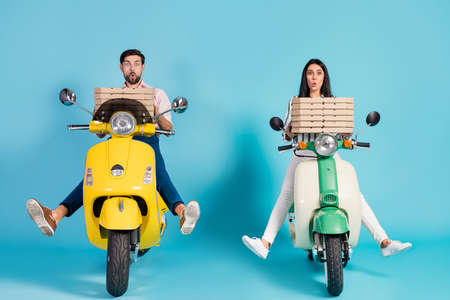 Brakes failed. Full length photo of crazy open mouth lady guy drive two vintage moped hold many paper pizza boxes courier profession isolated blue color background