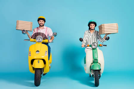 Full body photo of funny lady guy drive two vintage moped carry pizza boxes courier occupation junk fastfood formalwear outfit protective helmet isolated blue color background